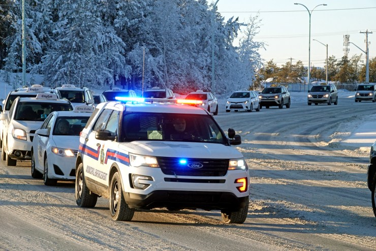 Municipal enforcement officers escort a parade of cab drivers through downtown Yellowknife