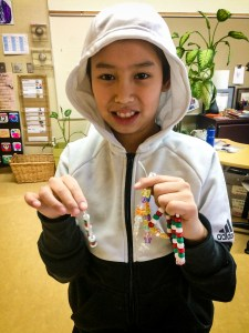 A student poses with jewellery created to help fund a water pump through UNICEF