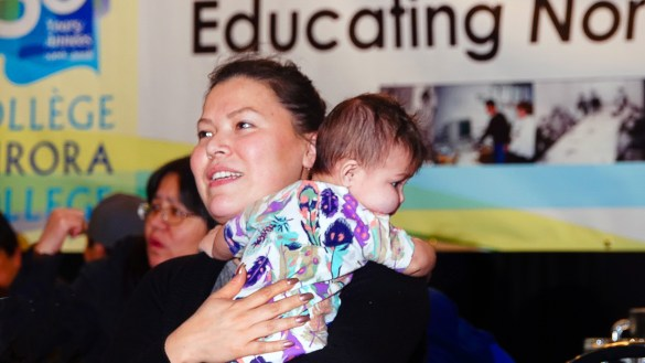 Jessica Deleary, who is taking an Indigenous revitalization course at the college, holds Heidi Desjarlais, a friend's toddler, during the dinner at the 50th Anniversary Drum Dance.