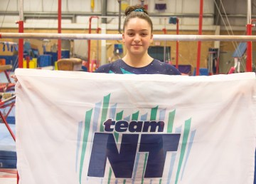 Maggie Carson holds Team NT's flag in this submitted photo. LeeAnna Carson/Photo