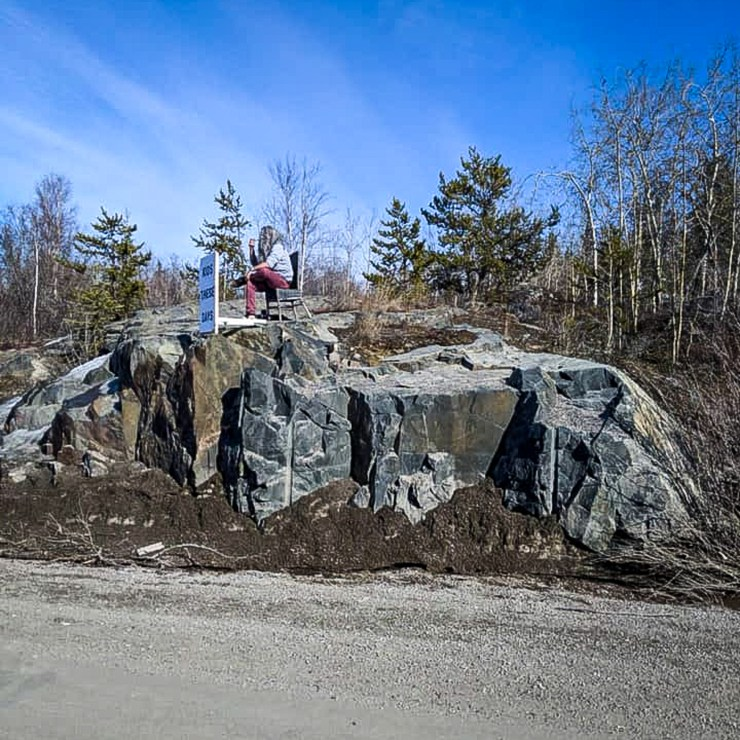 A man with a placard is seen on rocks next to a highway in Yellowknife