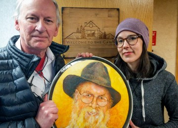 Bill Braden, left, and Sarah Swan with a Terry Pamplin portrait of Walt Humphries