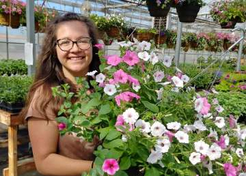Hilary Turko holds a hanging basket in her Roots and Ruminants greenhouse