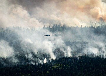 A helicopter drops water on a wildfire west of High Level in May 2019