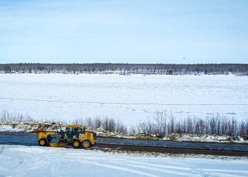 A grader passes along a Fort Simpson riverside road in March 2019