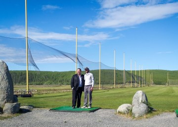 Industry minister Wally Schumann, left, and Inuvik golf club president Steve Krug stand in front of the town's driving range