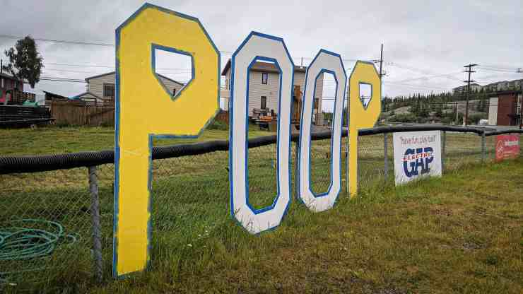 A large sign reading 'Poop' sits at a Yellowknife ballpark in July 2019