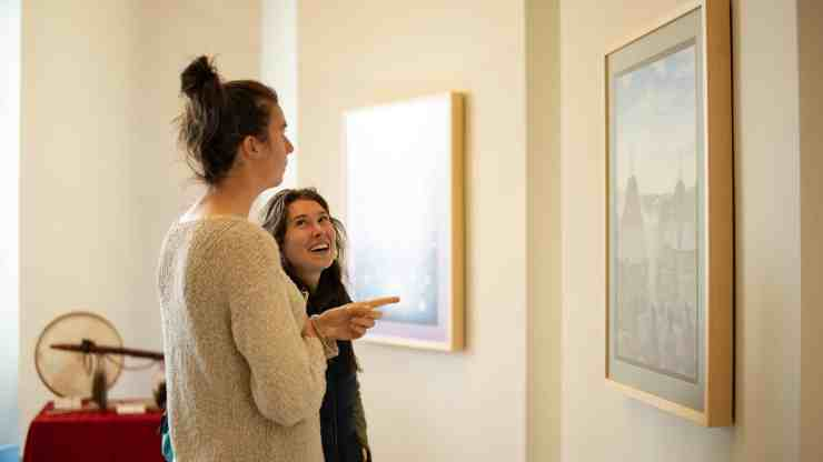 """Attendees chat about a painting by Behchokǫ̀'s Louis Angus Beaulieu called """"Circle of Wellness,"""" at the opening of the Stanton Territorial Hospital. Sarah Pruys/Cabin Radio"""