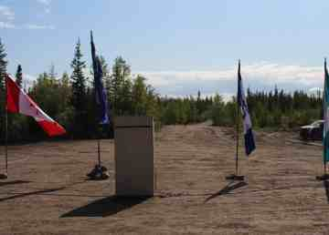 Canada, Tłı̨chǫ, NWT, and Whatì flags behind the podium at a ground-breaking ceremony for the Tłı̨chǫ all-season road on August 24, 2019