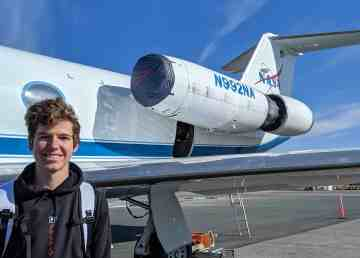 Aiden Rylott, a Grade 12 student in Yellowknife, stands beside a Nasa research jet on the airport's tarmac