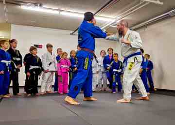 Instructors demonstrate in front of young participants at Yellowknife Brazilian Jiu Jitsu