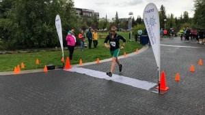 A runner crosses the finish line at the 2019 Overlander Marathon