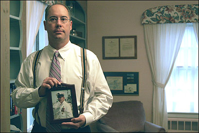 Kevin Adams, 39, of Marblehead, shown with a photo of his father in his military days, is headed for Army basic training.
