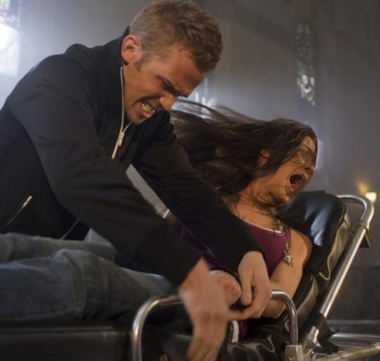 Mark (Cam Gigandet) rescues Casey (Odette Yustman) from an exorcism in a scene from ''The Unborn.''