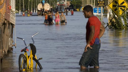 Residents in the northeast state of Maranhao moved along flooded streets yesterday. Thirty-six people have been killed.