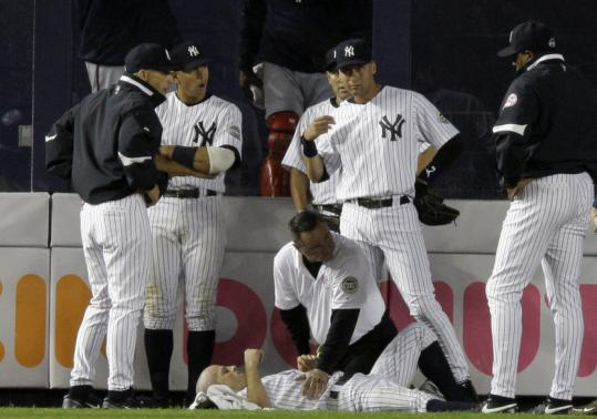 Yankees trainer Gene Monahan aids center fielder Brett Gardner, who hit his head on a plexiglass wall making a great catch in the eighth.