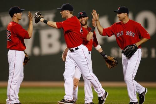 Red Sox second baseman Dustin Pedroia (second from right) and his Red Sox teammates celebrate the victory.