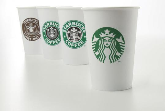 Cup (right) bears Starbucks' new logo. Other logos from years 1971, 1987, and 1992, (left to right) are also shown.