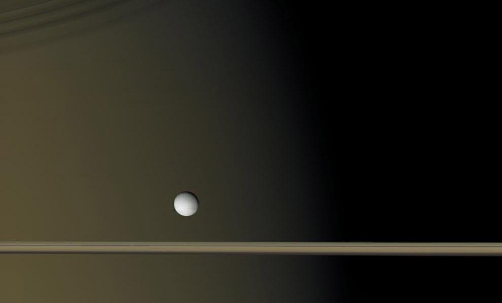 Encélado se cuelga como una única perla brillante contra el dorado-marrón lienzo de Saturno y sus anillos de hielo