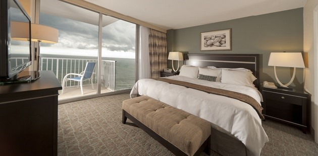 hotels with full kitchens in orlando florida counter height kitchen chairs oceanfront melbourne fl radisson suite hotel guest room king bed and a balcony overlooking the ocean