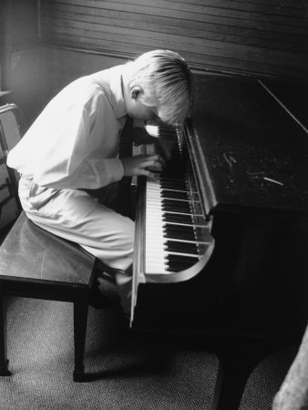 black and white photograph of boy about six playing grand piano
