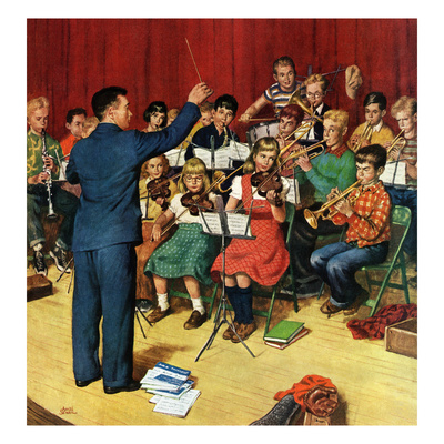 Male conductor in blue suit leading orchestra of elementary-aged children in folding chairs