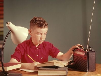 Boy with red hair and red shirt sits at dest with books, notebook, holding a pencil in his right hand, and adjusts a portable radio with his left hand. The room is sage green and a gooseneck lamp with a dark base and white shad is to the boy's right.
