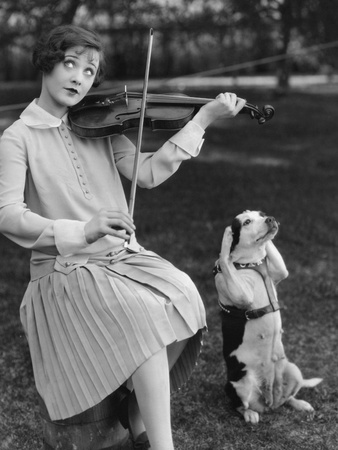 black and white photograph, woman with quizzical expression in 1920s day dress plays violin, brown and white dog sits up with its front paws over its ears