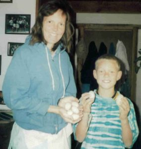 Mary Ann with son, Joshua, holding eggs from chickens