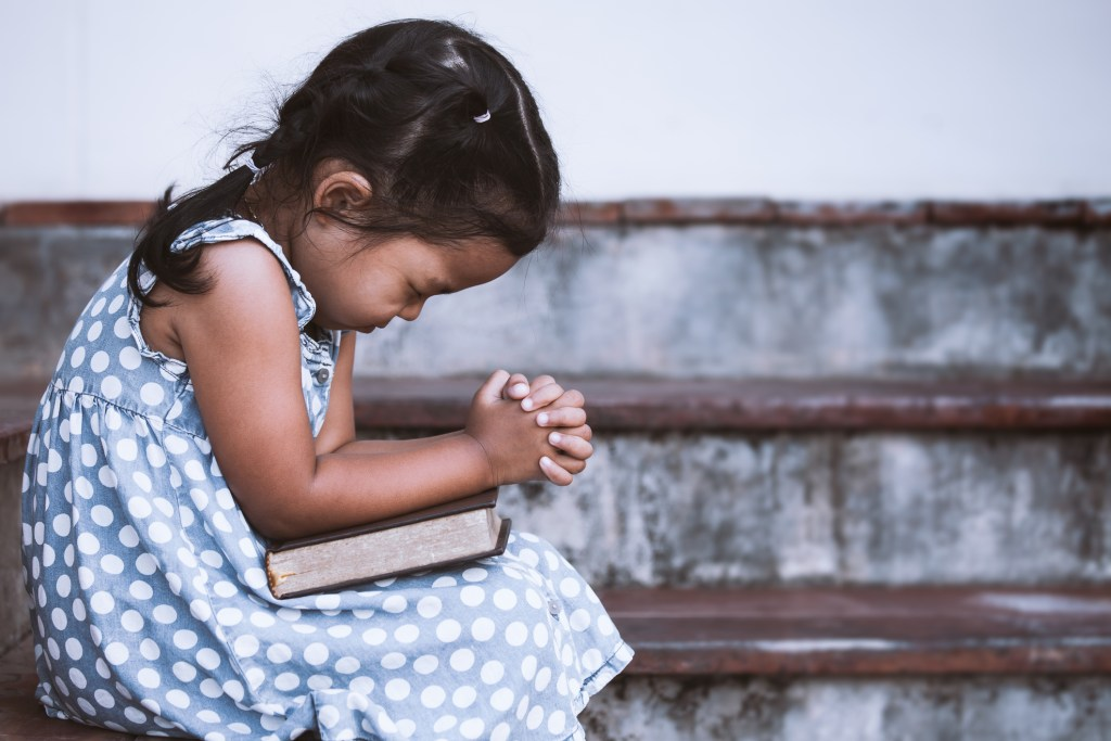 Cute little girl closed her eyes and  folded her hand in prayer on a Holy Bible
