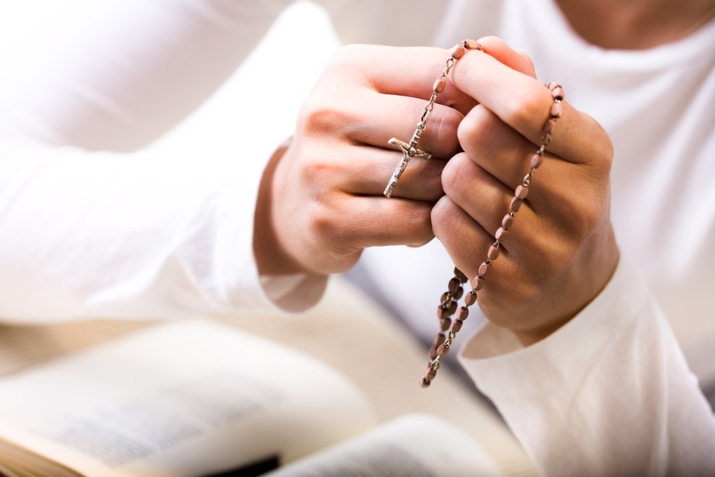Woman praying, holding rosary beads over bible