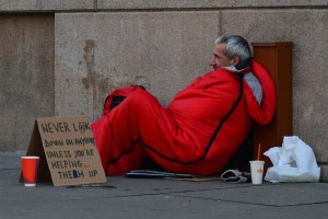 homeless man in sleeping bag begging