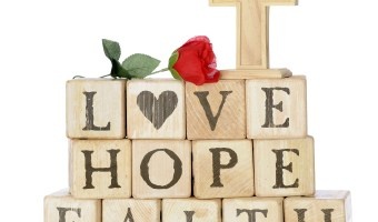 Rustic wood alphabet blocks arranged to say LOVE, HOPE and FAITH. They're topped with a red rose and a wood cross.