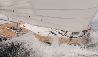 Close up of sailing boat, sail boat or yacht crashing through waves in a rough sea