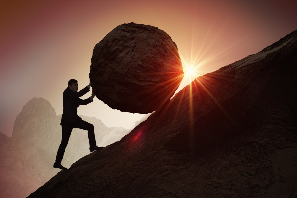 Silhouette of businessman pushing heavy stone boulder up on hill.