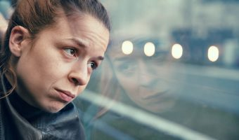 Sad woman looking out train window
