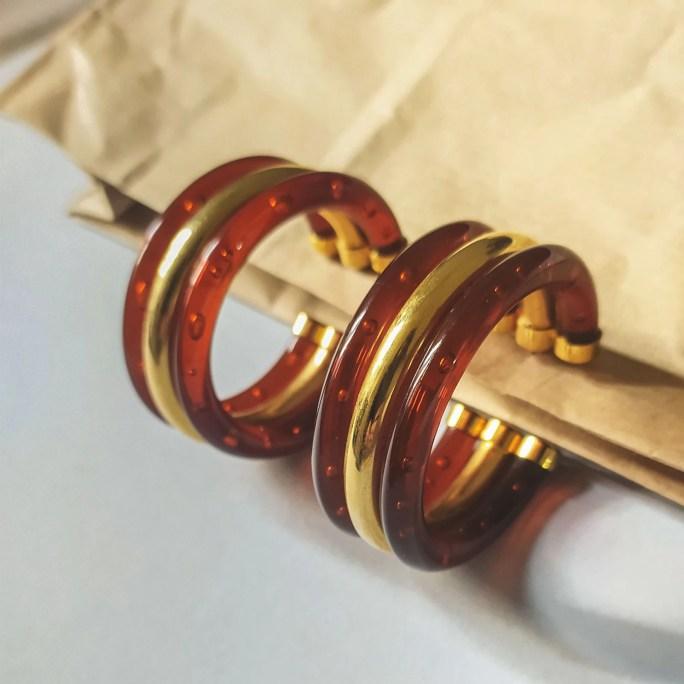 orecchini a cerchio oro e marrone su sfondo grigio e carta
