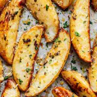 Crispy Garlic Baked Potato Wedges are soft pillows on the inside, and crunchy on the outside with a good kick of garlic and parmesan cheese!   http://cafedelites.com