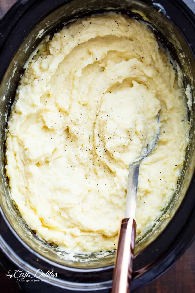 Creamy Slow Cooker Mashed Potatoes are incredibly easy to make! With a hint of garlic and parmesan cheese, this will become your favourite recipe! | http://cafedelites.com