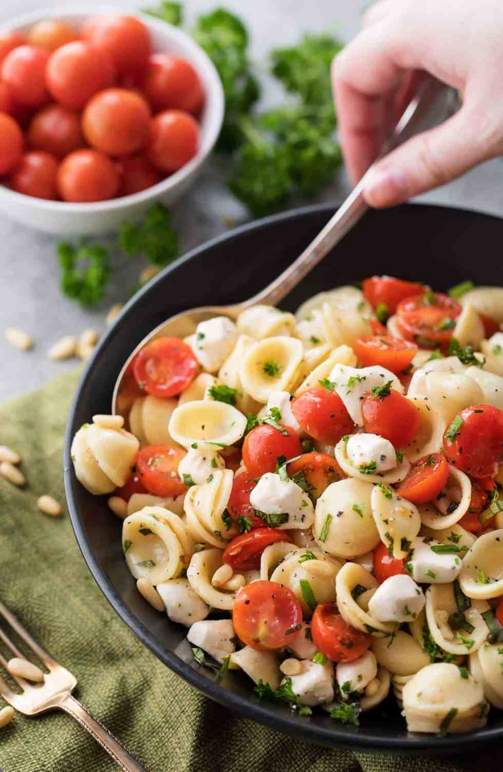The perfect Caprese pasta salad for a potluck or summer bbq! Caprese pasta salad made with juicy tomatoes, marinated fresh mozzarella cheese, fragrant fresh basil, and a mouthwatering homemade Italian herb vinaigrette! A versatile popular side dish!   cafedelites.com