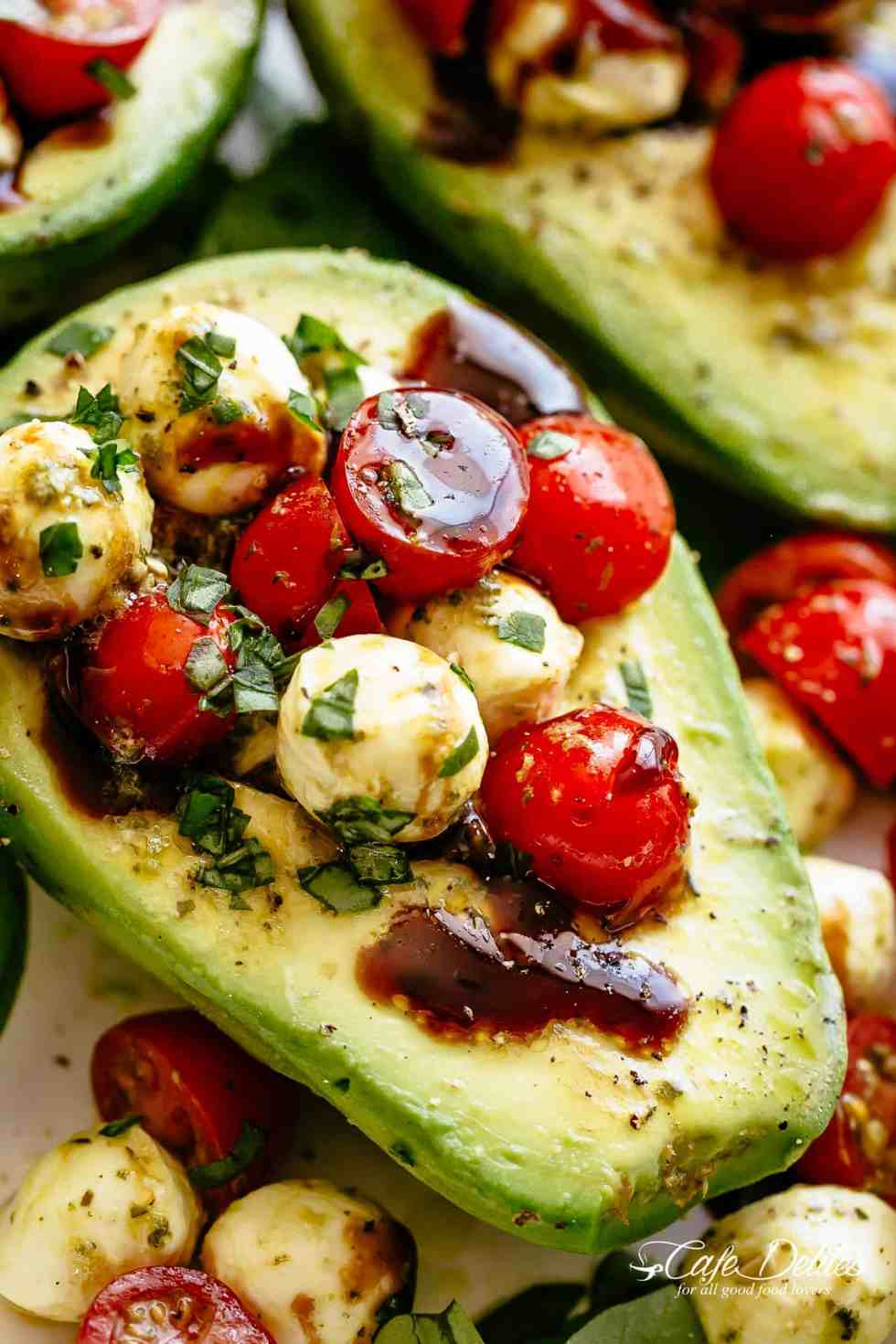 Basil Pesto Caprese Stuffed Avocado drizzled with balsamic glaze make an incredible light lunch or snack! Take creamy avocados to a different level! Sweet and juicy grape/cherry tomatoes with fresh mozzarella balls are tossed through basil pesto and spooned into avocado halves! | cafedelites.com