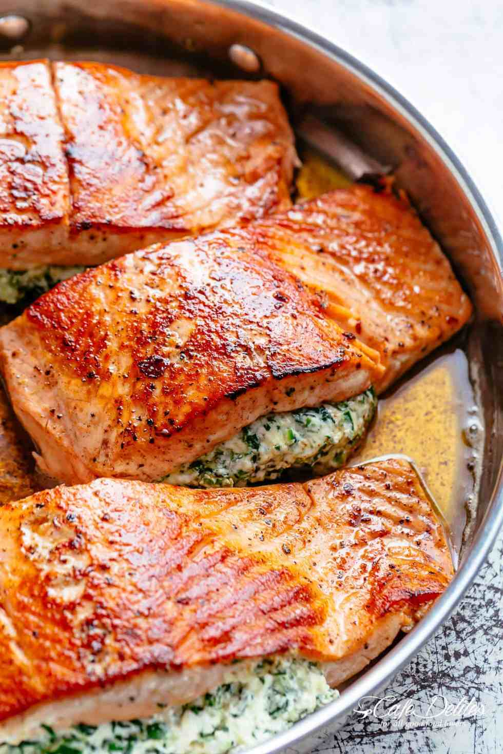 Creamy Spinach Stuffed Salmon in garlic butter is a new delicious way to enjoy salmon! Filled with cream cheese, spinach, parmesan cheese and garlic, this salmon beats than anything found in a restaurant. Your new favourite salmon recipe includes pan fried AND oven baked methods! | cafedelites.com