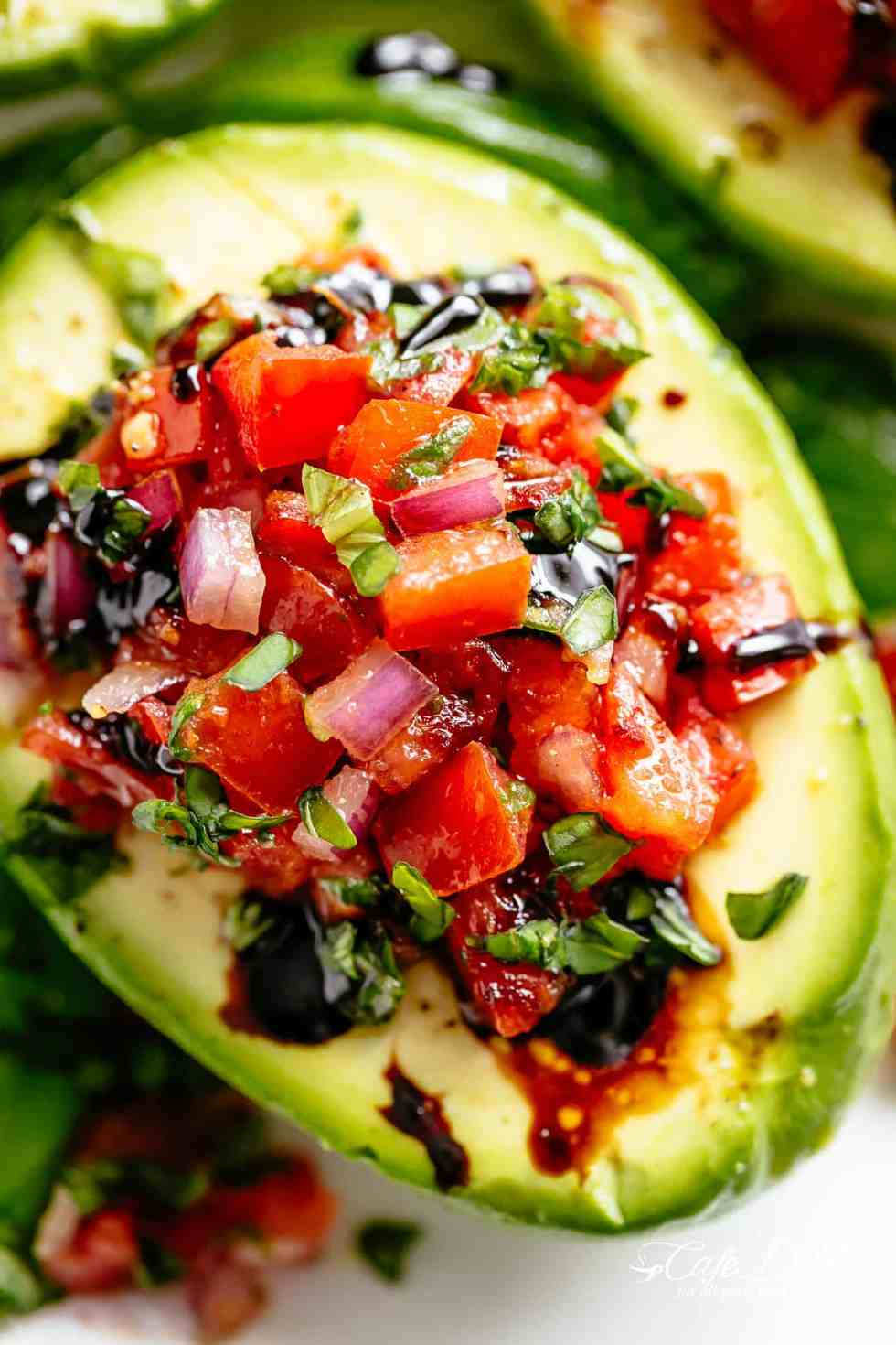 Take creamy avocados to a different level with Bruschetta Stuffed Avocados! Bruschetta tomato stuffed into Avocados with parmesan and a balsamic reduction! | cafedelites.com