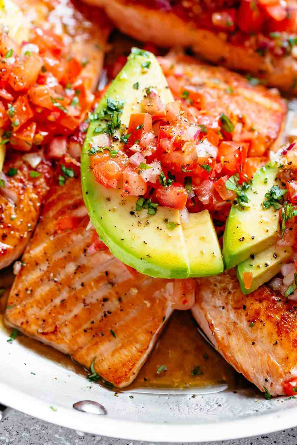 Pan Seared Salmon in a buttery garlic lemon sauce, topped with a fresh tomato salsa and avocado slices! Healthy and low carb!   cafedelites.com