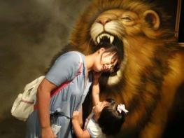 A-woman-puts-her-head-in-the-mouth-of-a-lion-at-the-Trick-Art-Museum-in-Korea