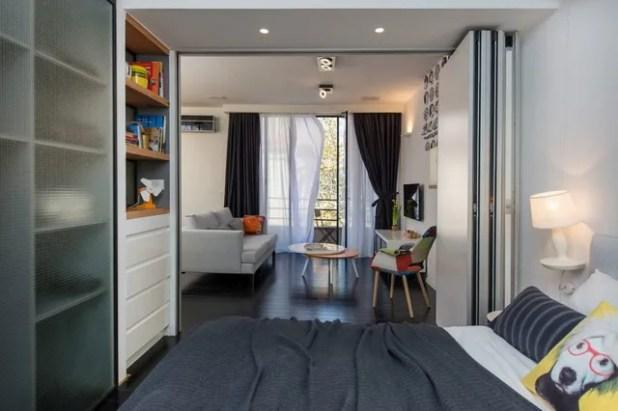 Phòng ngủ rộng thoáng thông ra phòng khách khi chiếc cửa gấp được mở rộng tối đa.