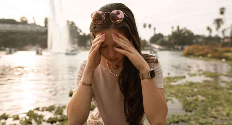 distressed woman sitting on lakeside and touching face in despair