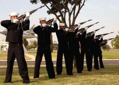 A Navy Honor Guard renders a twenty-one gun salute during a memorial service .