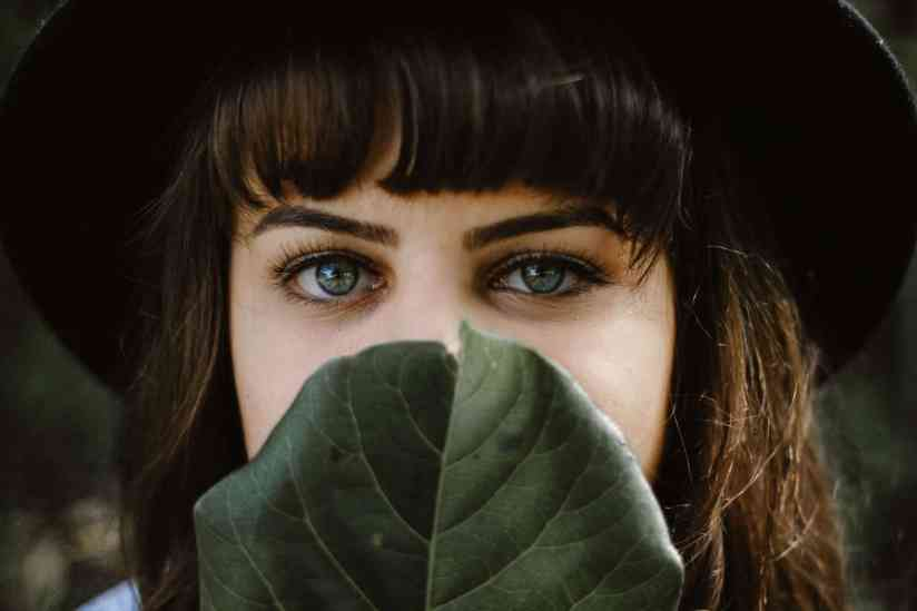 Perfect career choices for introverts. Photograph of a young woman hiding half her face.