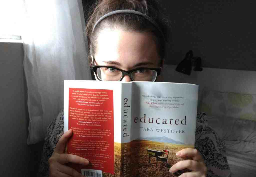 """A photograph of me peaking over a book, """"Educated"""" by Tara Westover."""